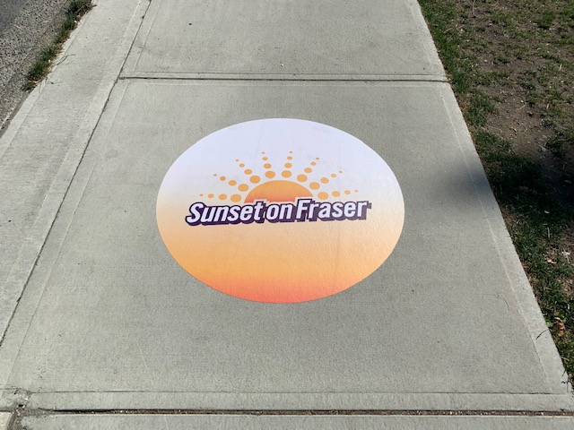 A sidewalk decal featuring the Sunset on Fraser logo