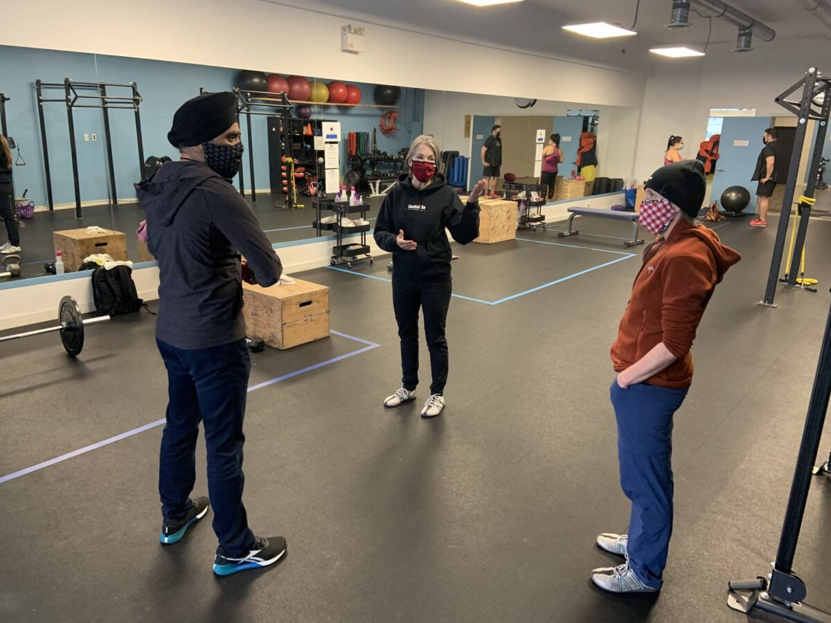 Minister Harjit Sajjan speaks with Eastside Fitness co-owners Wendy Sinclair and Darnelle Moore